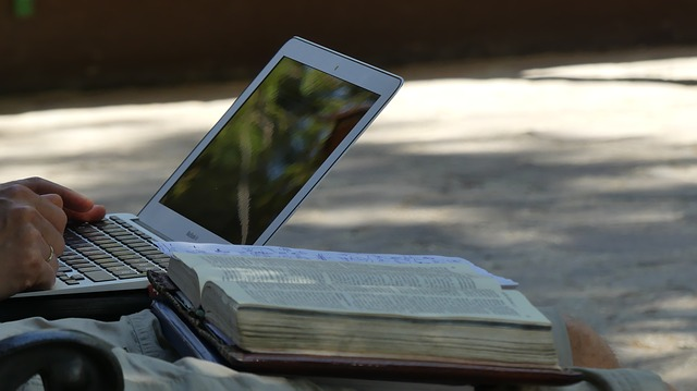 Young Person on Laptop and Reading Bible